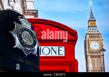 Close view on Metropolitan police helmet with Houses of Parliament and red telephone box behind Westminster London - Stock Photo