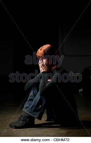 teen girl sitting on a floor in a darkened room looking depressed - Stock Photo