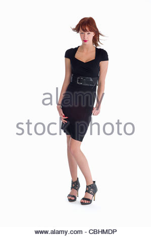 Teen girl fashion model in a black dress on a white background. - Stock Photo