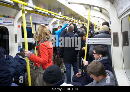 girl with red coat standing on busy tube train surrounded by people on london underground england united kingdom - Stock Photo