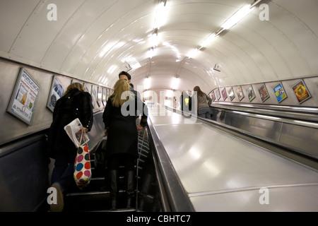 passengers and commuters going up on the escalator at a london underground tube station england united kingdom uk - Stock Photo