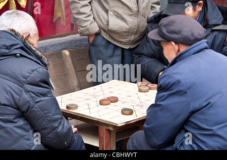 Chinese old men playing chinese chess (xiangqi) - Stock Photo