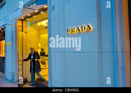 Paris, France, Luxury Clothing Shopping, Prada Store, Woman Leaving Entrance, Avenue Montaigne, Store front door, - Stock Photo