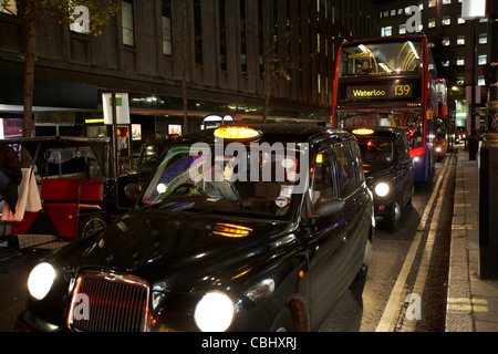 row of black london cabs taxis and busses at night stuck in traffic on shopping street in central london england - Stock Photo