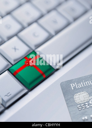 Detail of a keyboard with one key wrapped up as a Christmas gift and a credit card at the bottom right corner. - Stock Photo