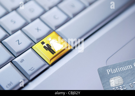 Detail of a laptop keyboard with a bride and groom symbol on a gold key and a credit card at the bottom right corner - Stock Photo