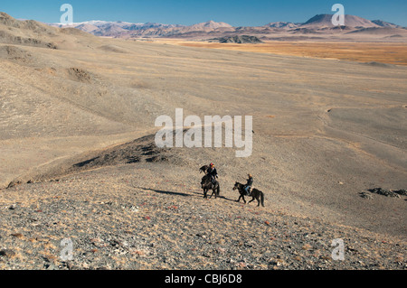 Kazakh eagle hunters riding with their golden eagles in the Altai Region of Bayan-Ölgii in Western Mongolia - Stock Photo