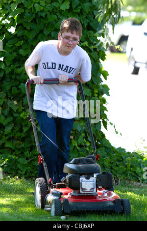Teenage boy mowing a lawn in Boise, Idaho, USA. MR - Stock Photo