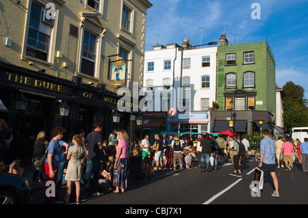 Corner of Elgin Crescent and Portobello Road streets on busy Saturday market day Notting Hill district London England - Stock Photo