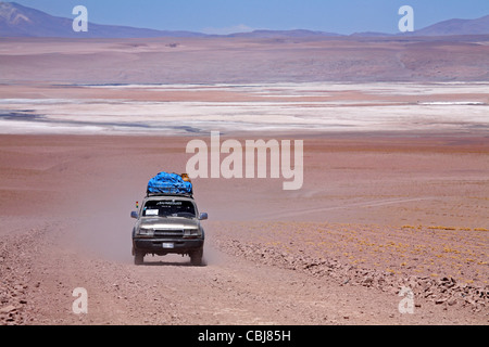 Four-wheel drive vehicle driving on dirt-track on the Altiplano in Bolivia - Stock Photo