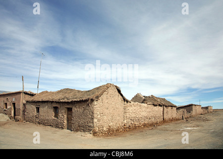 Street corner and adobe houses with thatched roofs in the village Colchani on the high plateau Altiplano, Bolivia - Stock Photo