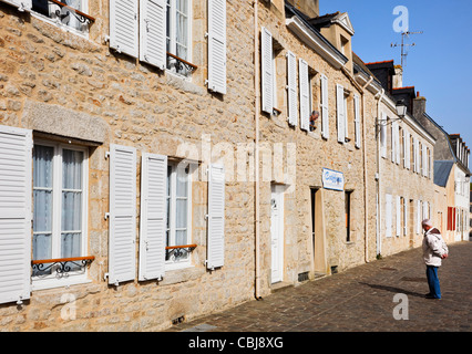 Man talking to a woman in a window in Port Louis, Brittany, France - Stock Photo