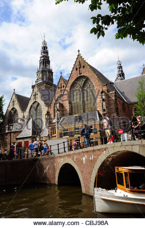 Bridge crossing town canal in the Wallen-quarter, Oudezijds Voorburgwal, Oude Kerk church, Amsterdam, the Netherlands, - Stock Photo