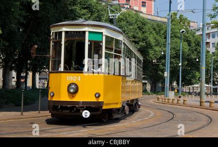 historic classic yellow tram of Milan on winding rails, Italy - Stock Photo