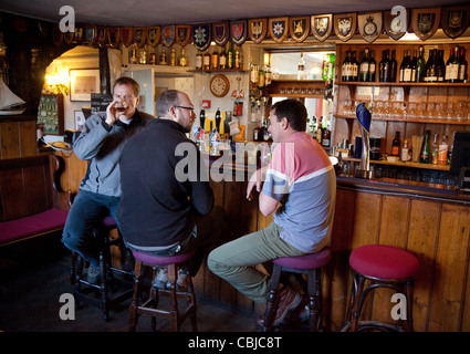 Three men drinking and talking in a  bar, The Jolly Sailor pub, Orford village Suffolk UK - Stock Photo