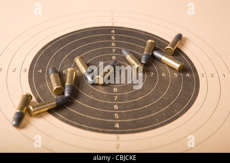Target and several .22 caliber bullets (focus on center) - Stock Photo