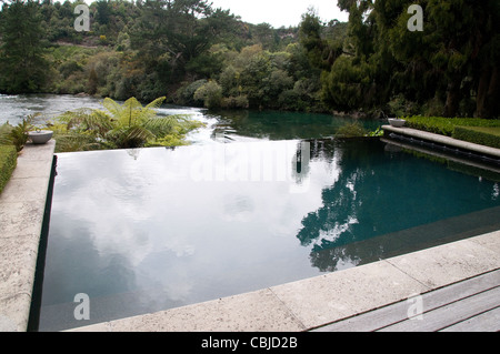 A resort infinity pool lies on the banks of the Waikato River near Huka Falls in the Lake Taupo region of New Zealand. - Stock Photo