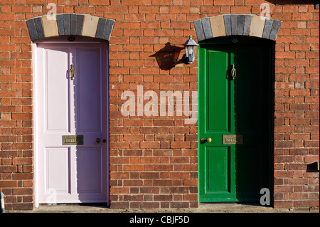 White and green front doors Nos 43 and 42 of period terraced houses in Kington Herefordshire England UK - Stock Photo