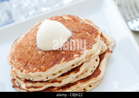 Fresh buttermilk pancakes with scoop of butter on white plate - Stock Photo