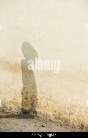 Young rural Indian village boys shadow on a sun lit wall. India - Stock Photo
