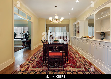 Dining room in luxury home with white cabinetry - Stock Photo