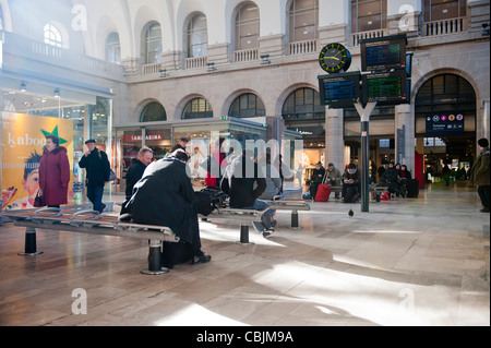 People sitting in a waiting area in the Gare de l'est train rail railway station in Paris, France. - Stock Photo