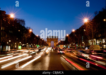 A wide-angle view Arc de Triomphe from Champs Elysees during evening, featuring light trails from traffic. - Stock Photo