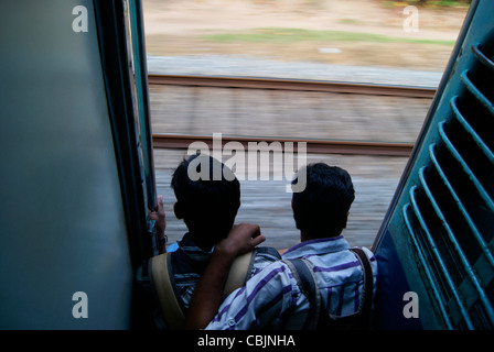 Two young friends sitting dangerously in a fast moving train illegally in steps of hard metallic door entrance - Stock Photo