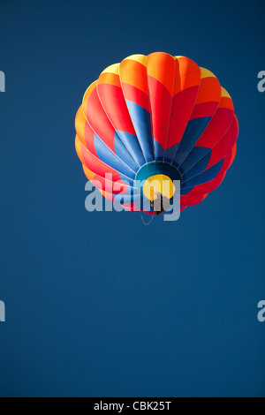 Hot Air Balloon in flight, clear blue sky - Stock Photo