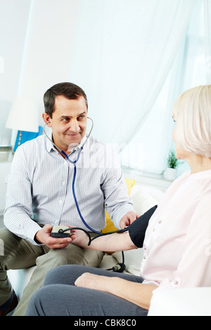 Portrait of mature man measuring blood pressure of his wife at home - Stock Photo
