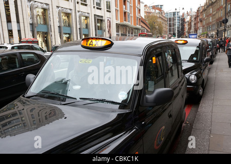 row of black london cabs taxis for hire on knightsbridge shopping street in central london england united kingdom - Stock Photo