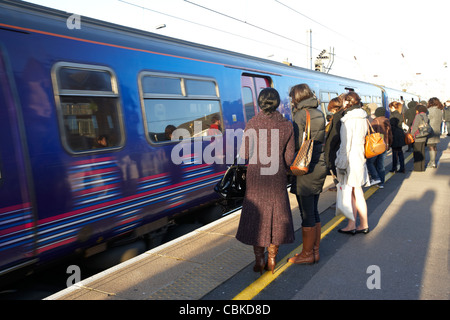 people waiting to board arriving train at cricklewood rail train station london england united kingdom uk - Stock Photo