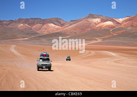 Four-wheel drive vehicles driving on dirt-track on the Altiplano in Bolivia - Stock Photo