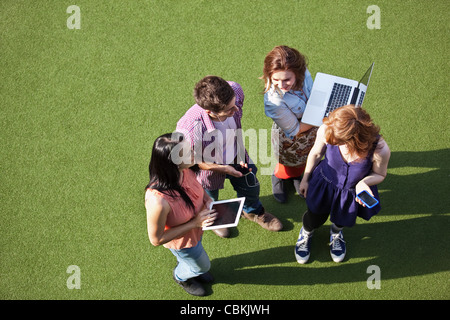 Four people standing on asto turf with technological equipment - Stock Photo