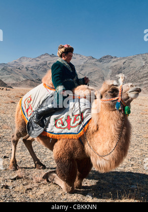 Kazakh man and his Bactrian camel on the Central Asian Steppe at the Kazakh Eagle Hunters' Festival in Bayan-Ölgii, - Stock Photo