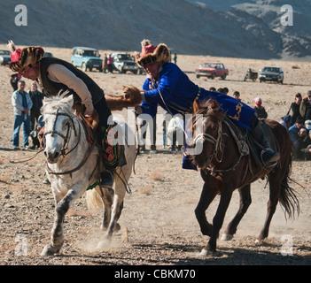 Kazakhs playing kokbar, a traditional sport, at the Eagle Hunter's festival in Mongolia - Stock Photo
