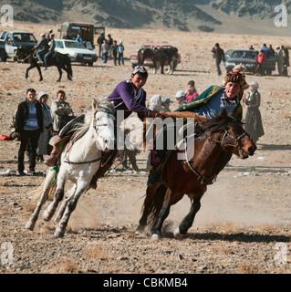 Kazakhs playing kokbar, a traditional sport at the Eagle Hunters Festival in Bayan-Ölgii in Western Mongolia - Stock Photo