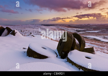 Millstones in snow at Sunset on Stanage Edge, Peak District National Park, Derbyshire, England, UK - Stock Photo