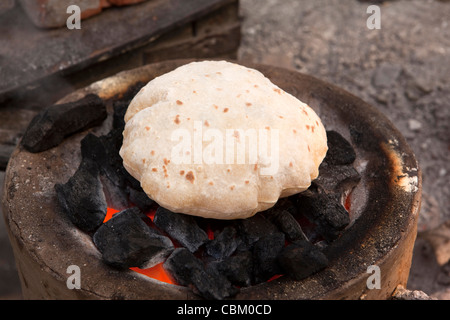 India, West Bengal, Kolkata, Esplanade, cooking, roti being puffed up in fire coals at bus station food stall - Stock Photo