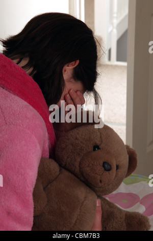Girl wearing a pink dressing gown, wiping tears from her eyes, holding a teddy bear. - Stock Photo