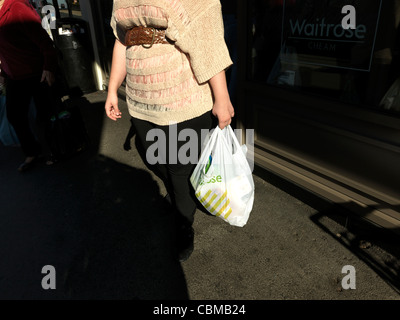 Woman Coming Out Of Waitrose Supermarket Carrying Food In Plastic Recyclable Shopping Bag Cheam Village England - Stock Photo