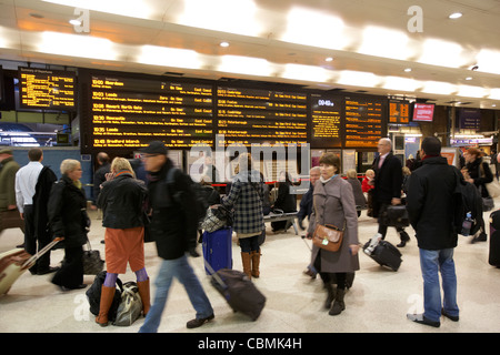 people rushing past local and national train information boards at king's cross rail station london england united - Stock Photo