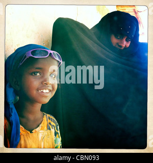 Mature Woman In Dark Dress With Little Girl Wearing Sunglasses On Forehead, Degehabur, Somaliland - Stock Photo