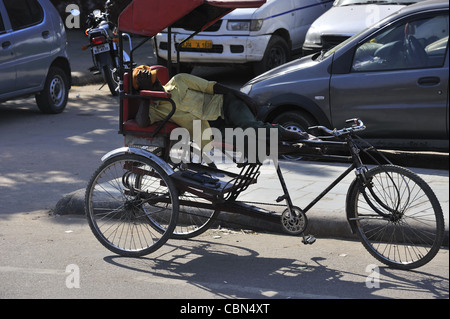 Bicycle rickshaw driver sleeping on a street in Agra India - Stock Photo