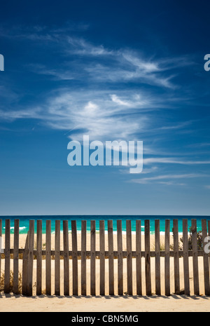 sky with clouds on the beach with a wooden fence - Stock Photo