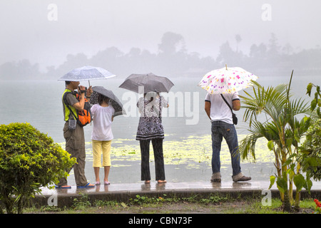 Tourists with umbrellas on a rainy day walk on a path at Beretan Lake, Bali, Indonesia - Stock Photo