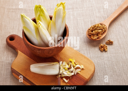 whole chicory in wooden bowl on a wooden board with knife and wooden spoon with walnuts - Preparing a chicory and - Stock Photo