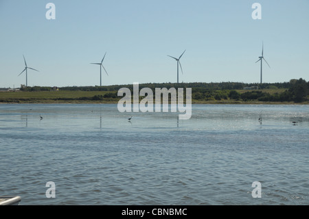 Windmills rotate on a ridge in North Lake Harbor Prince Edward Island, Canada. - Stock Photo