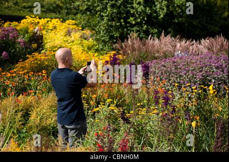 Man taking a photograph in The Hot Garden in September, RHS Rosemoor, Devon, England, United Kingdom - Stock Photo