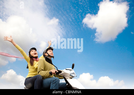 Happy young couple having fun on a scooter - Stock Photo